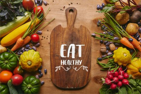 "Photo for Cutting board with ""eat healthy"" lettering and summer vegetables on wooden table - Royalty Free Image"