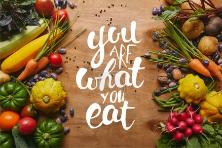 "Photo for Frame of healthy food vegetables and beans on wooden table with ""you are what you eat"" lettering - Royalty Free Image"