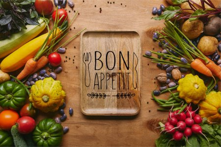"Organic raw vegetables and tray with ""bon appetit"" lettering on wooden table"