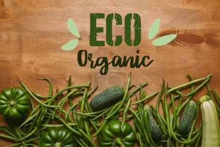 "Green beans and organic vegetables on wooden table with ""eco organic"" lettering"