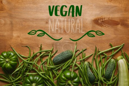 """Judías verdes y verduras orgánicas en mesa de madera con letras """"veganas naturales"""""""