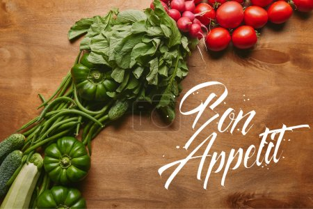 """Green and red summer vegetables on wooden table with """"bon appetit"""" lettering"""