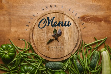 """Photo for Organic raw green vegetables with wooden cutting board with """"healthy menu"""" lettering - Royalty Free Image"""
