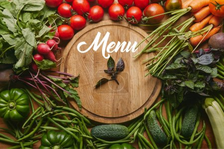 """Photo for Variety of fresh vegetables and herbs by cutting board with """"menu"""" lettering - Royalty Free Image"""