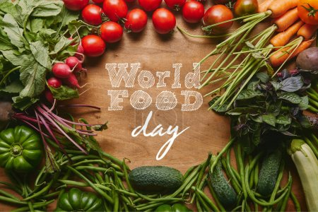 "Frame of healthy green and red vegetables on wooden table with ""world food day"" lettering"