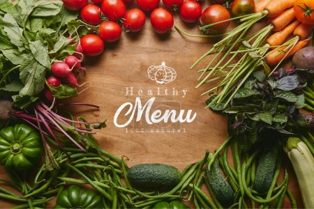 "Photo for Frame of healthy green and red vegetables on wooden table with ""healthy menu"" lettering - Royalty Free Image"