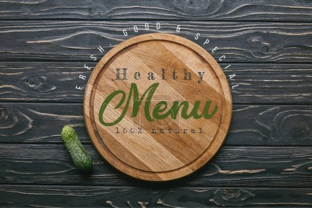"""Cutting board with """"healthy menu"""" lettering and cucumber on dark wooden table"""