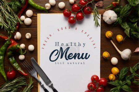 """top view of card with """"healthy menu"""" lettering, cutlery and fresh herbs with vegetables on wooden surface"""