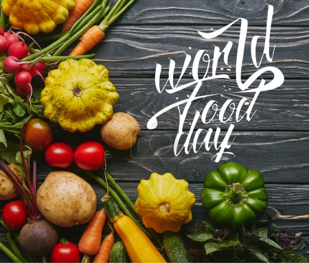 "Organic raw vegetables on dark wooden table with ""world food day"" lettering"