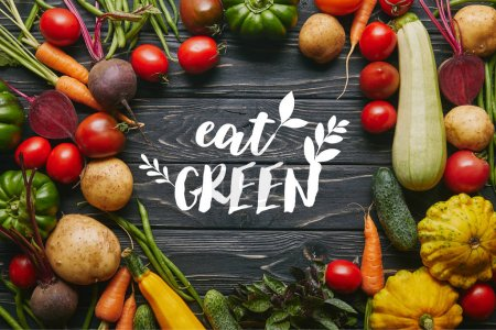 "Frame of healthy summer vegetables on dark wooden table with ""eat green"" lettering"