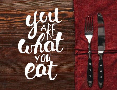 haut de la page vue des fourchettes et des couteaux sur une nappe rouge foncée sur fond en bois avec «vous êtes ce que vous mangez» lettrage