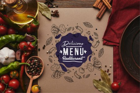 """Photo for Top view of card with """"delicious menu restaurant"""" lettering, spices and vegetables on wooden surface - Royalty Free Image"""