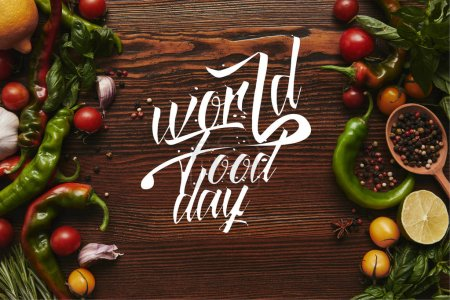 "top view of fresh healthy vegetables and spices on wooden background with ""world food day"" lettering"