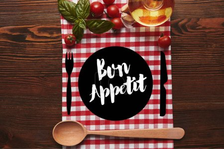 """top view of checkered tablecloth, wooden spoon and fresh basil with tomatoes and oil on wooden surface with """"bon appetit"""" lettering"""