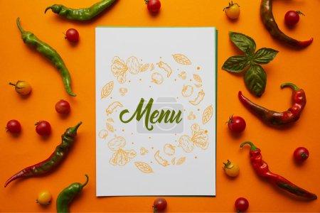 Photo pour Vue de dessus de la carte avec le lettrage «menu» et tomates fraîches, basilic et poivrons sur orange - image libre de droit