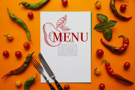 "Photo for Top view of card with ""menu"" lettering and avocado, cutlery and fresh tomatoes with basil and peppers on orange - Royalty Free Image"