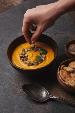 Photo pour Plan recadré de main humaine et délicieuse soupe à la citrouille dans un bol - image libre de droit