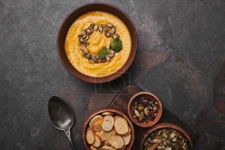bowl with tasty pumpkin soup, spices, rusks, pumpkin seeds and spoon on dark surface