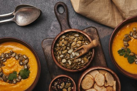 top view of healthy pumpkin seeds, spices, rusks and tasty pumpkin soup in bowls