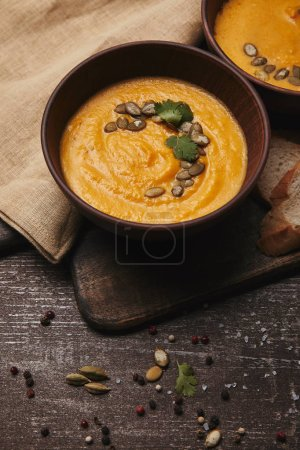 close-up view of healthy organic pumpkin soup in bowls on rustic wooden table