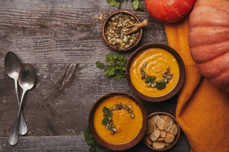 Photo for Top view of delicious pumpkin soup in bowls, spoons, fresh pumpkins and rusks on wooden table - Royalty Free Image