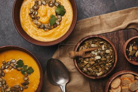 top view of bowls with pumpkin soup, spoons, rusks and pumpkin seeds on wooden table
