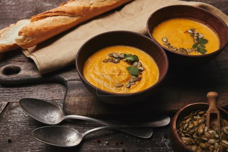 Photo pour Vue rapprochée des bols avec soupe à la citrouille, cuillères et graines de citrouille sur une table en bois - image libre de droit