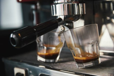 close-up view of professional coffee maker and two glasses with espresso