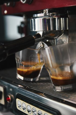 close-up view of professional coffee machine and two glasses with espresso