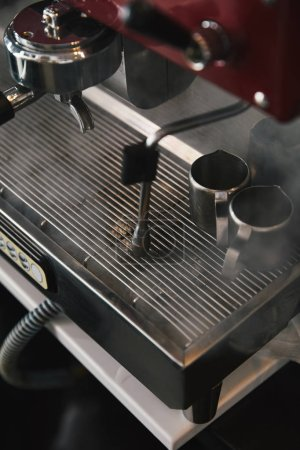 close-up view of professional coffee machine with steam in coffeehouse