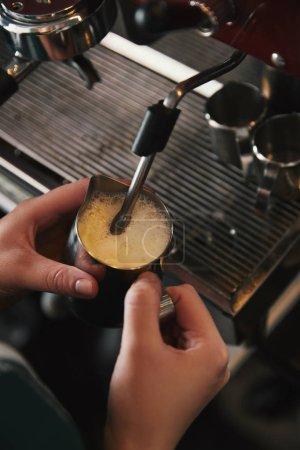 cropped shot of barista preparing cappuccino in coffee machine