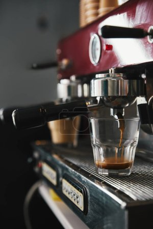 close-up view of professional coffee maker and glass cup with espresso