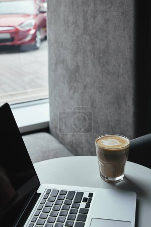 close-up view of laptop with blank screen and cup of cappuccino on table in cafe