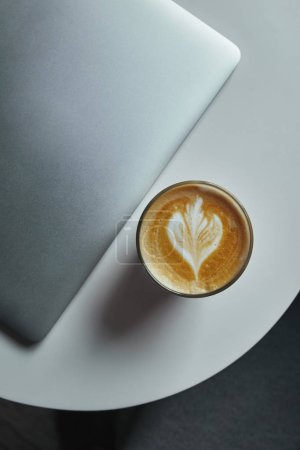 Photo for Top view of laptop and cup of coffee on table - Royalty Free Image