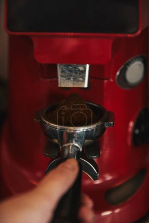cropped shot of barista preparing espresso in coffee machine