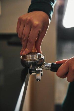 cropped shot of barista preparing espresso in coffee maker