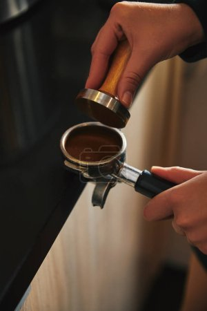 close-up partial view of barista preparing coffee in coffee maker