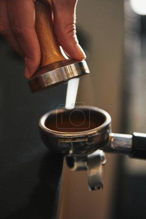 cropped shot of barista preparing coffee in coffee maker