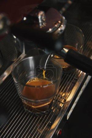 close-up of coffee machine preparing espresso in two cups