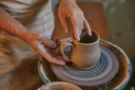 Photo for Cropped image of professional potter working on pottery wheel at workshop - Royalty Free Image