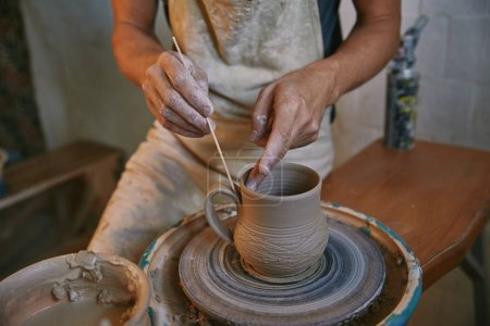 cropped image of man decorating clay pot at workshop