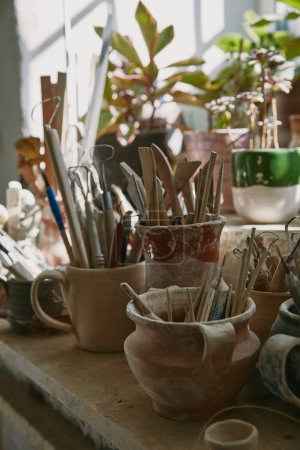 selective focus of pottery tools and paintbrushes at table in pottery studio