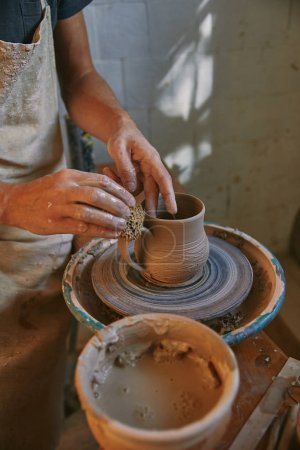 cropped image of potter working on pottery wheel at workshop
