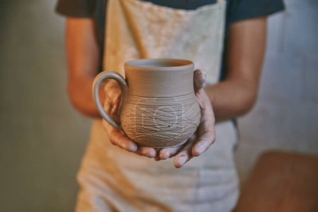 selective focus of man holding clay pot in pottery studio