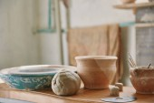selective focus of clay and pottery tools at table in workshop