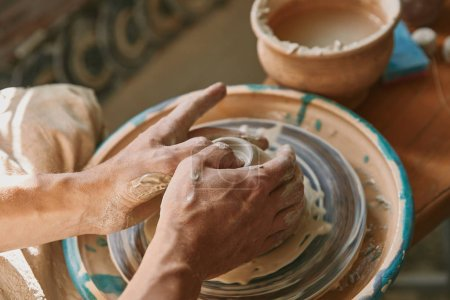 close up view of man hands working on pottery wheel at workshop