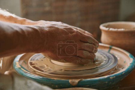 selective focus of male potter hands working on pottery wheel at workshop