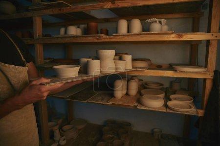 Foto de Imagen recortada de potter en delantal poniendo platos y cuencos de cerámica en estantes en taller - Imagen libre de derechos