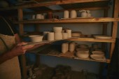 cropped image of potter in apron putting ceramic bowls and dishes on shelves at workshop