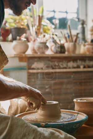 cropped image of male potter working on pottery wheel at workshop
